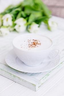 白いカップと白いチューリップのセイロンシナモンとコーヒーカプチーノ