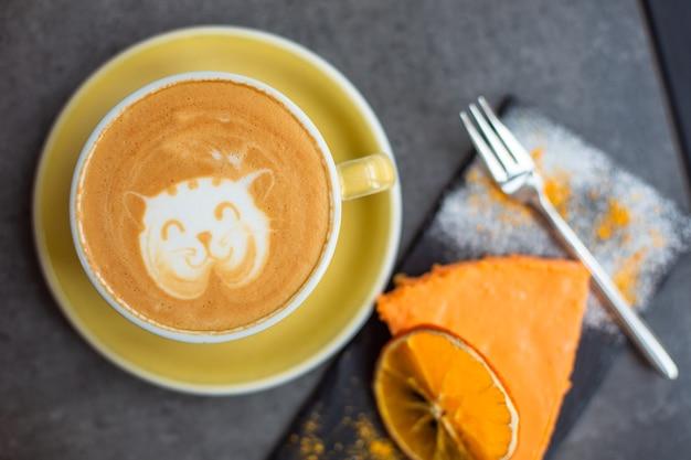 Кофе капучино в желтой чашке с сырным пирогом в кафе