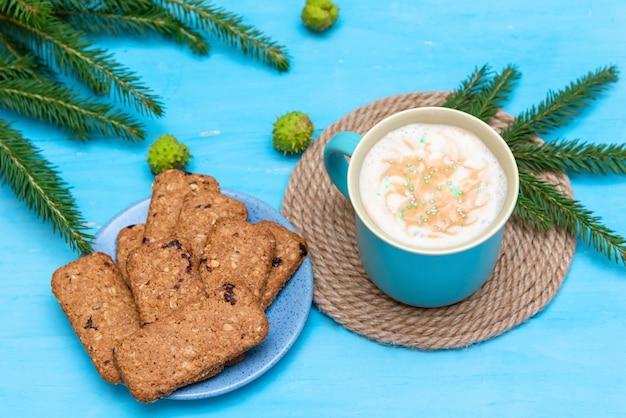 水色の背景にオートミールクッキーとコーヒーのクリスマスドリンク。