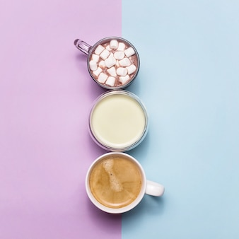 Coffee, cocoa and matcha with white creamers of milk on blue
