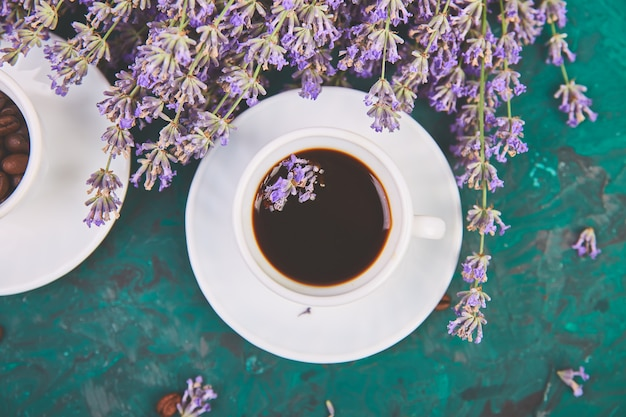 Coffee, coffee grain in cups and lavender flower on green table from above. good morning concept. woman working desk. cozy breakfast. mockup. flat lay style