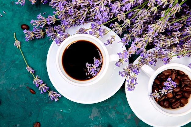 Coffee, coffee grain in cups and lavender flower on green