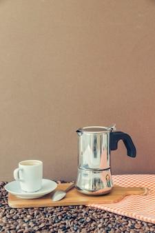 나무 보드에 컵과 모카 포트와 커피 구성