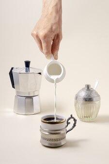 Концепция кофе - наливание молока в чашку кофе, гейзерную кофеварку и шугар