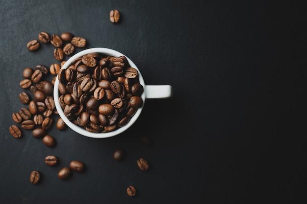 暗いテーブルの上のカップにコーヒー豆とコーヒーの概念。上面図。
