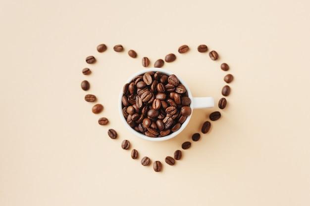 파스텔 표면에 심장 모양의 원두 커피와 커피 개념