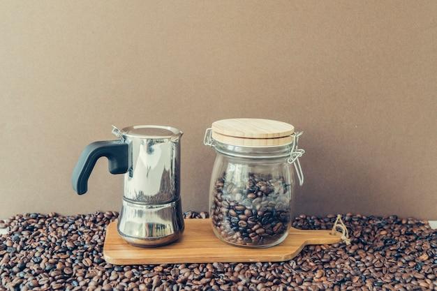 Coffee concept with moka pot and jar on board