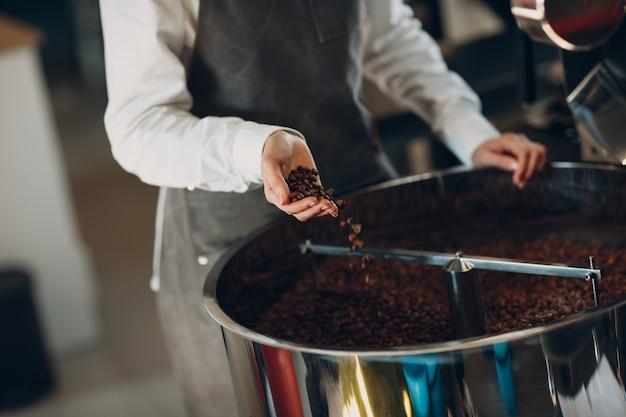 コーヒー焙煎工程での焙煎機でのコーヒー冷却。若い女性労働者バリスタコーヒー豆を手に混ぜて持ちます。