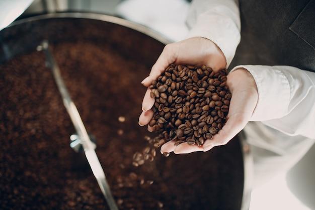 커피 로스팅 과정에서 로스터 기계에서 커피 냉각. 젊은 여성 작업자 바리스타 커피콩을 손에 들고 믹싱합니다.