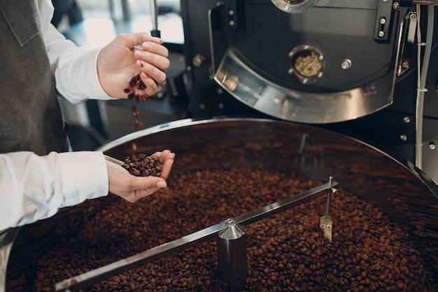 커피 로스팅 과정에서 로스터 기계에서 커피 냉각. 젊은 여성 노동자 바리 스타 혼합 커피 콩.