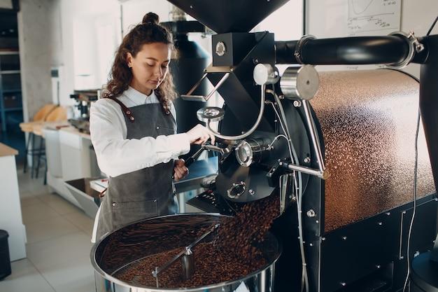 커피 로스팅 과정에서 로스터 기계에서 커피 냉각. 젊은 여성 작업자 바리스타 믹싱 냉각 커피 콩