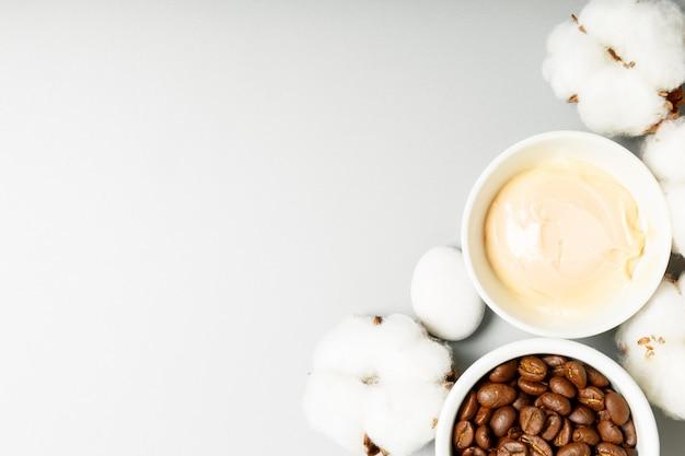 コーヒークリーム、コーヒー豆、灰色の背景に綿。自然化粧品と美容のコンセプト。トップビュー、フラットレイアウト、コピースペース。