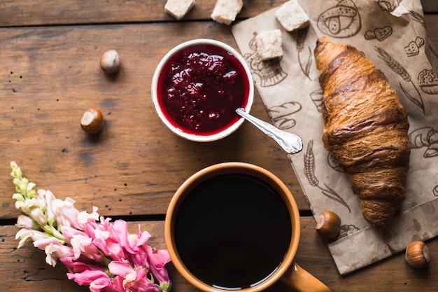 古い木製のテーブルの上のコーヒークロワッサン