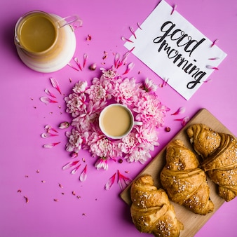 Coffee and croissant on a pink background