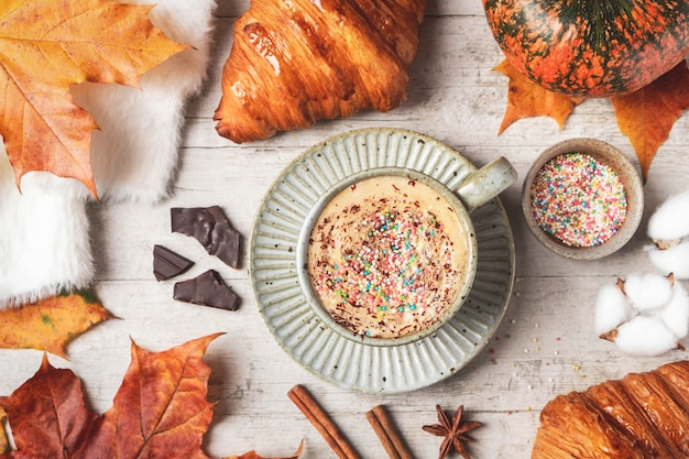 Coffee, croissant, pumpkin, white fluffy sweater on a white background and maple autumn leaves. autumn concept.