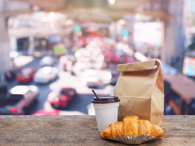 Coffee and croissant with paper bag on wooden table over blurry traffic