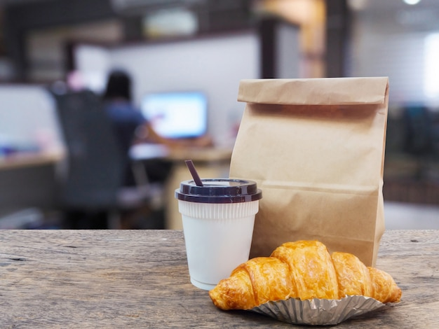 Coffee and croissant with paper bag on wooden table