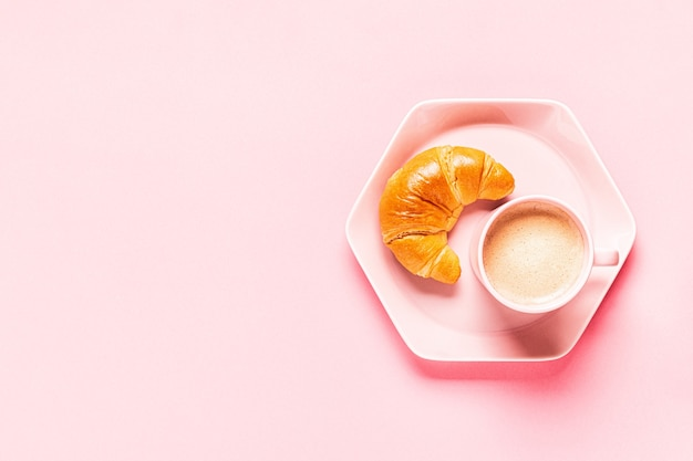 Coffee and croissants for breakfast on a pink background, top view,