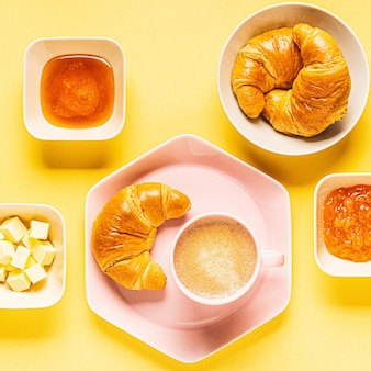 Coffee and croissants for breakfast on a yellow background, top view, flat lay.