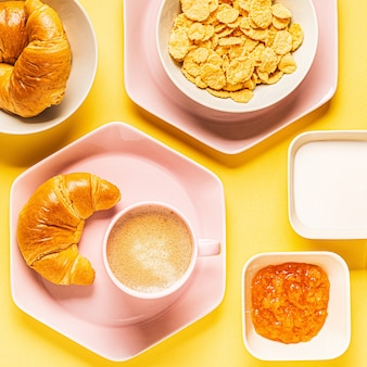 Coffee and croissants for breakfast on a yellow background, top view,