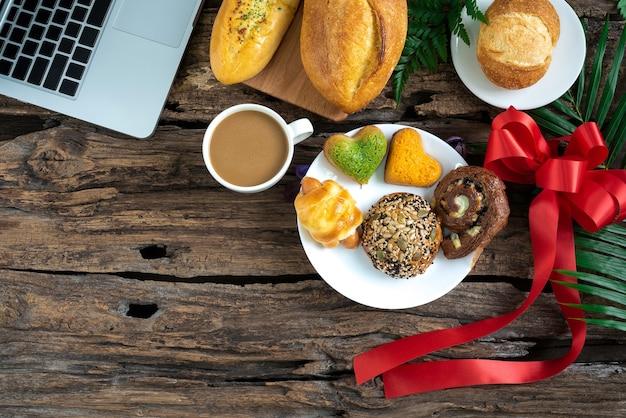 커피 크로와상 시나몬 롤과 딸기 아침 식사 나무 테이블에 메모장이 있는 tex용 메모장