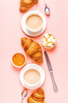 Coffee and croissants on pastel background, top view.