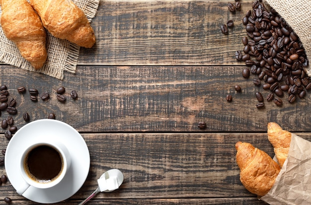 Coffee, croissants, roasted coffee beans on a wooden board with copy space. mock up for coffee background.