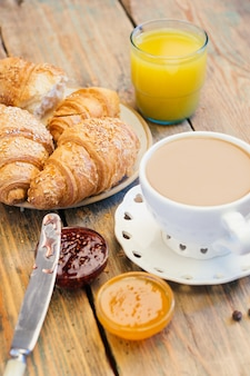Coffee and croissants with jam and orange juice. typical french breakfast (petit déjeuner)
