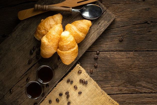 Coffee and croissants on the wooden background, top view