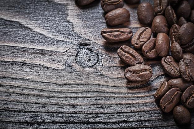 Кофейные зерна на винтажной деревянной доске еды и питья концепции