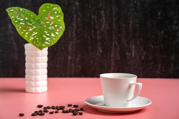 白い花瓶の織り目加工のカラジュームの葉に対するコーヒーカップ。