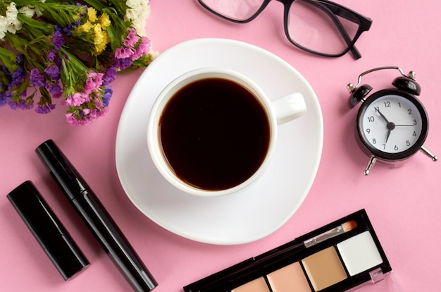 Coffee cup, alarm clock, flowers, mascara and glasses on pink surface.