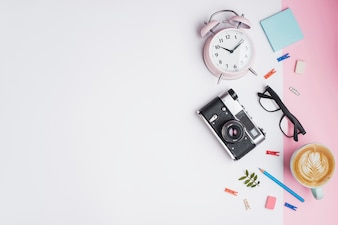 Coffee cup; alarm clock; retro camera; eyeglasses and retro camera on white and pink dual backdrop