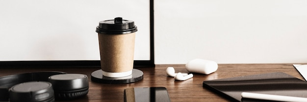 나무 책상 위의 커피 컵과 디지털 태블릿