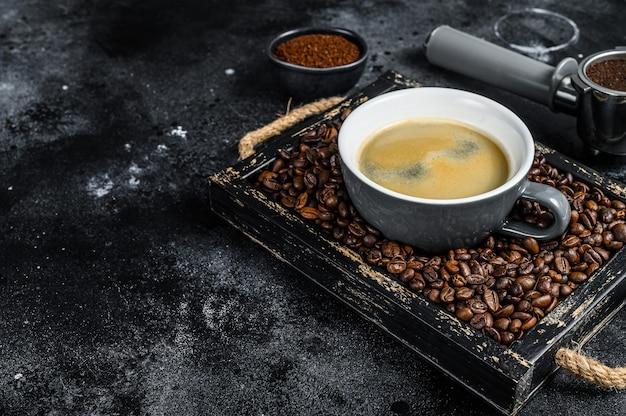 커피 컵과 블랙 테이블에 오래 된 나무 쟁반에 콩. 평면도.