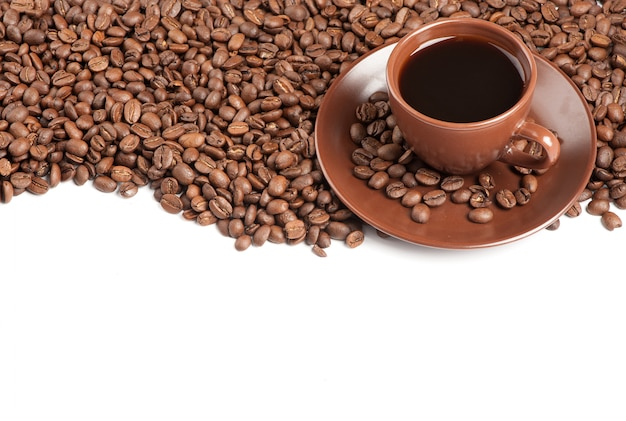 コーヒーカップと白い背景の上の豆