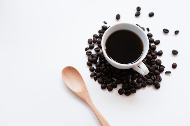 Чашка кофе и бобы на белом фоне.