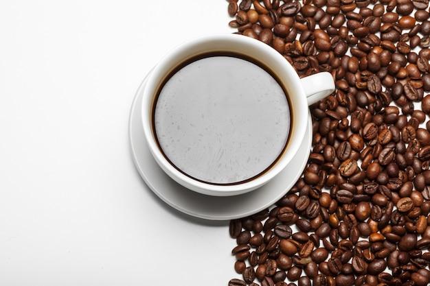 Чашка кофе и бобы на белом фоне