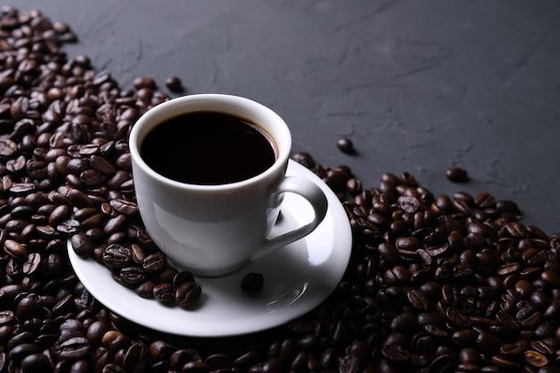 Чашка кофе и бобы на старом сером кухонном бетоне