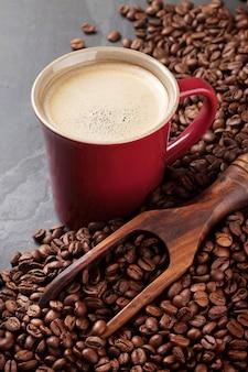 石のテーブルの上のコーヒーカップと豆