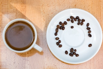 Coffee cup and beans on wooden background
