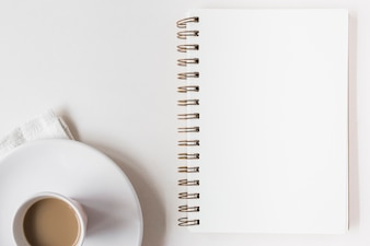 Coffee cup and blank spiral notepad on white background