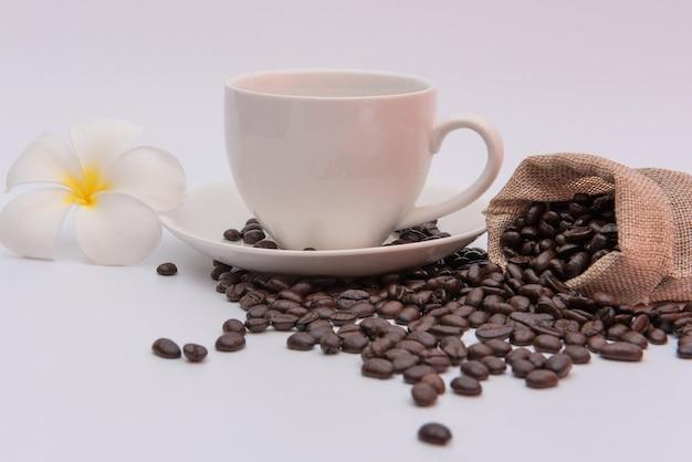 プルメリアの花と白いテーブルの上のコーヒーカップとコーヒー豆