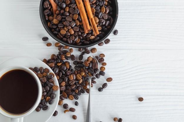 白い木製のテーブルの上のコーヒーカップとコーヒー豆