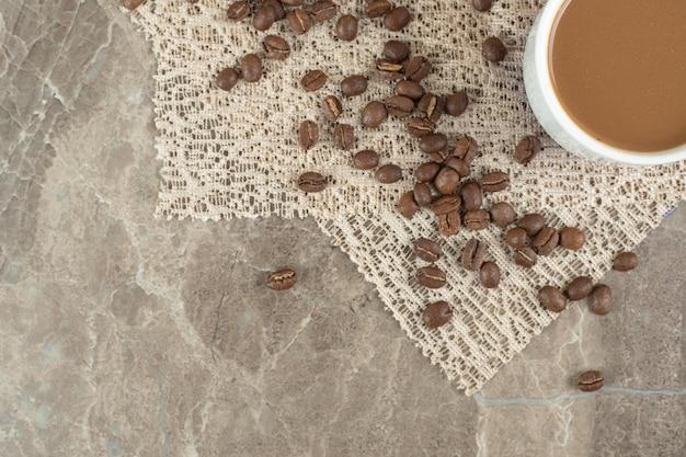 黄麻布と大理石の表面にコーヒーカップとコーヒー豆