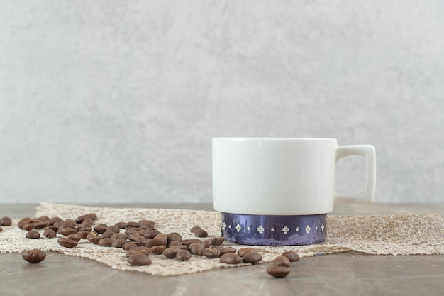 커피 컵과 대리석 테이블에 커피 콩입니다.