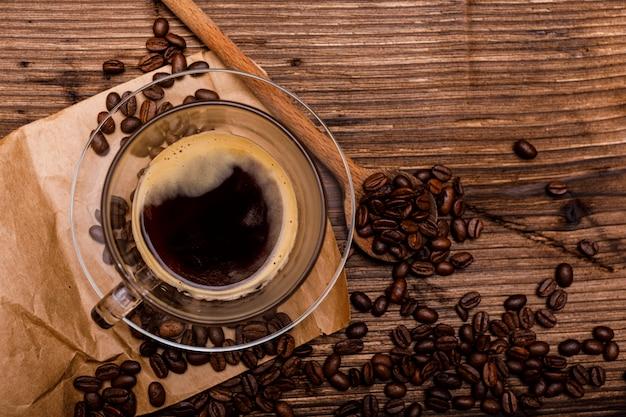 Кофейная чашка и кофейные зерна на старой деревенской деревянной предпосылке. вид сверху с копией пространства для текста.