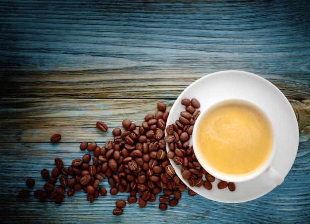 古いぼろぼろの木製の背景にコーヒーカップとコーヒー豆。