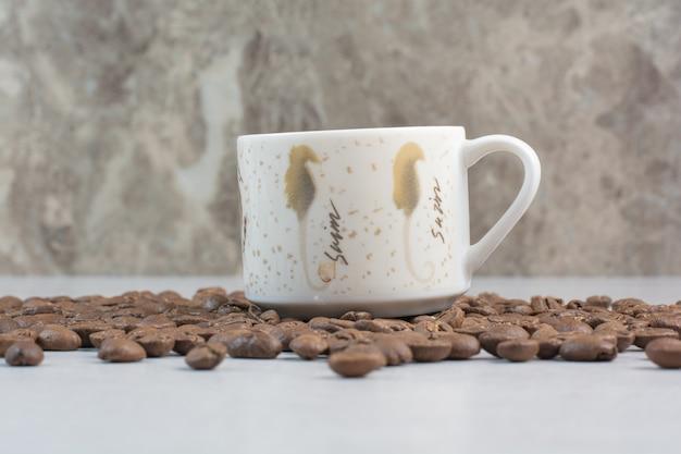 커피 컵과 흰색 바탕에 커피 콩입니다. 고품질 사진