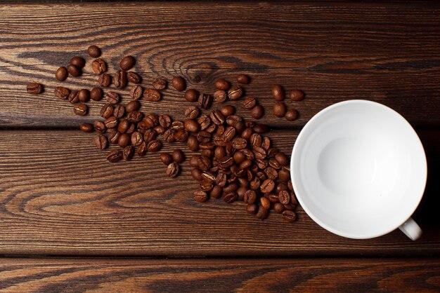 Чашка кофе и кофейные зерна на деревянных фоне. вид сверху.